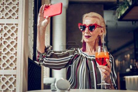 Photo pour Humeur parfaite. Femme âgée gentille prenant un selfie tout en appréciant sa journée parfaite - image libre de droit