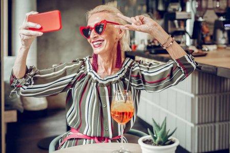 Photo pour Beau look. Joyeuse femme âgée portant des lunettes de soleil élégantes tout en prenant des photos d'elle-même - image libre de droit