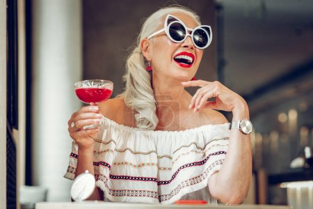 Photo pour Jolie boisson. Joyeux femme agréable profiter de son cocktail de fantaisie tout en étant assis avec son verre à la table - image libre de droit