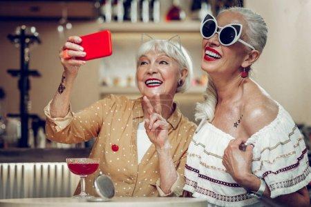 Photo pour De vieux amis. Femmes âgées heureuses souriant tout en posant pour le selfie ensemble - image libre de droit