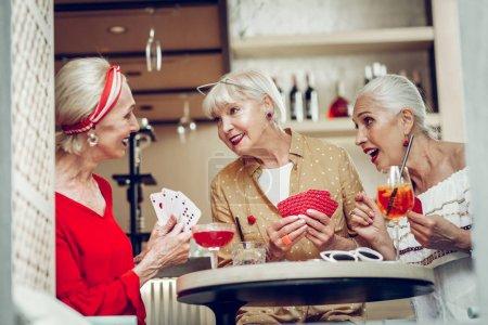 Photo pour Tant de plaisir. Amis féminins positifs boire des cocktails tout en jouant à des jeux de cartes ensemble - image libre de droit