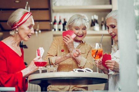 Photo pour Jeu de cartes. Heureuses femmes âgées tenant leurs cartes tout en jouant ensemble dans un jeu - image libre de droit