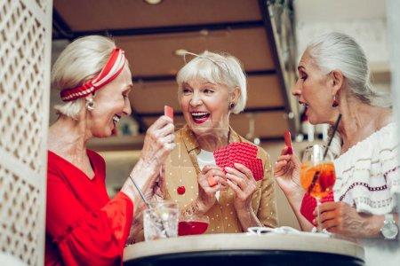 Photo pour Activité agréable. Femmes joyeuses positives assis autour de la table tout en appréciant leur jeu de cartes - image libre de droit