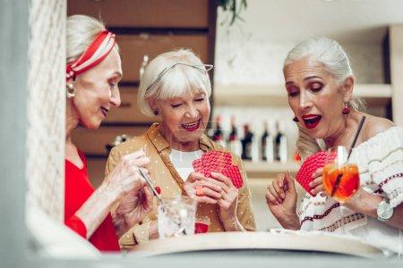 Photo pour Tant de plaisir. Heureuses femmes âgées s'amuser tout en jouant aux cartes ensemble - image libre de droit