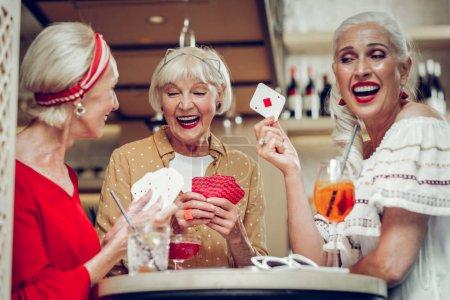Photo pour De vieux joueurs. Délicieuses femmes âgées s'amusant ensemble tout en appréciant le jeu - image libre de droit