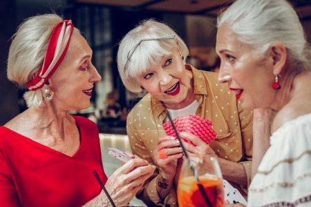 Photo pour Agréable interaction. Belles femmes agréables parlant entre elles tout en jouant aux cartes ensemble - image libre de droit