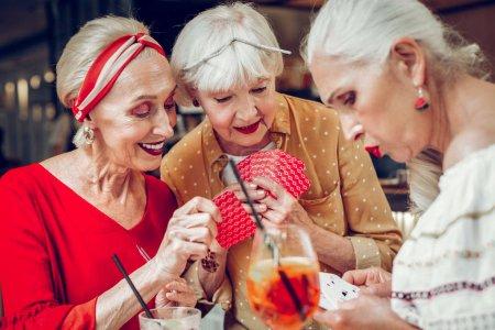 Photo pour Un jeu amusant. Joyeuses femmes âgées tenant leurs cartes tout en jouant au poker ensemble - image libre de droit