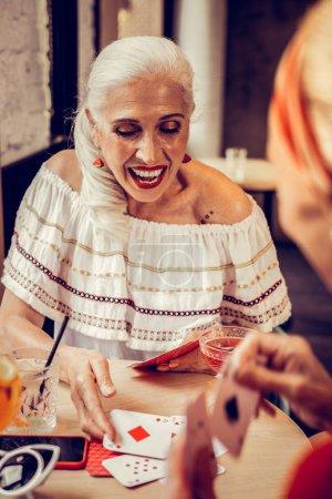 Photo pour Humeur de jeu. Femme âgée aux cheveux longs excitée avec rouge à lèvres brillant et haut blanc exposant ses cartes - image libre de droit