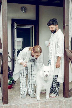 Photo pour Une routine de deuil. Heureux mariés mi-adulte joyeux conjoints gais portant un pyjama debout près de la maison de campagne et caressant un chien blanc moelleux le matin . - image libre de droit