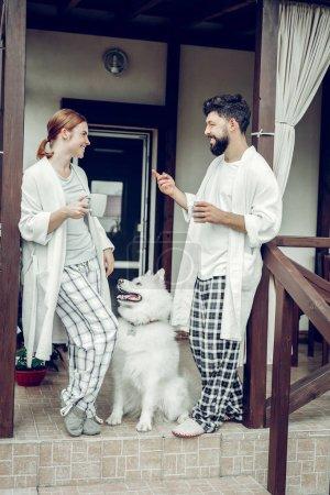 Photo pour Bonjour à la maison. prétendu rayonnant agréable attrayant actif mi-adulte marié couple dans les vêtements de nuit profiter du café du matin tandis qu'un moelleux grand samoyed sucré assis à côté . - image libre de droit