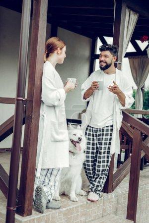 Photo pour Les propriétaires de chiens. Joyeux rougeoyant beau regard énergique charmant époux aimants portant les vêtements de nuit avoir la conversation et tenant tasses à café du matin tandis qu'un chien assis près d'eux . - image libre de droit