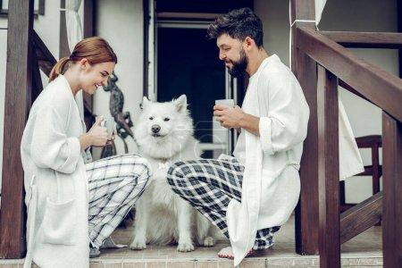 Photo pour Assis avec un chien. Joyeux calme joyeux beau couple mi-adulte ayant une conversation tout en étant assis au seuil de la porte avec un beau samoyed blanc . - image libre de droit