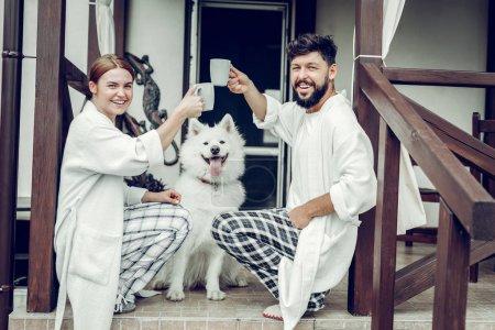 Photo pour Passer la matinée ensemble. Contesté rayonnant joyeux mi-adulte mari et femme portant le pyjama cliquetis matin tasses à café tout en étant assis sur les marches du chalet avec un chien . - image libre de droit