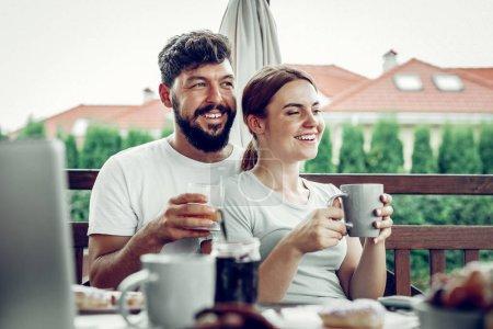 Photo pour Des épouses aimantes. Heureux joyeux mari souriant attrayant aux cheveux bruns embrassant tendrement son beau conjoint envoûtant aux cheveux roux pendant le petit déjeuner dans le jardin - image libre de droit