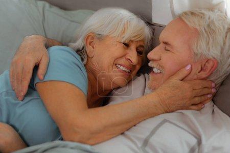 Photo pour Serrant et couché dans le lit. Photo en gros plan de séduisante séduisante séduisante affectueuse aux cheveux argentés vieillissement ridé mari et femme tendrement étreignant et couché dans le lit . - image libre de droit