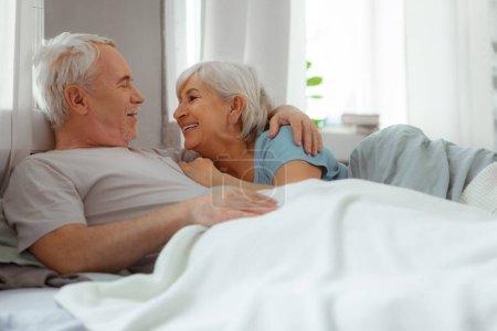 Photo pour Embrasse affectueusement ta femme. Rayonnant beau beau attrayant homme barbu aux cheveux argentés dans le t-shirt en ivoire embrassant amoureusement son sourire âgé joyeux conjoint aux cheveux courts - image libre de droit