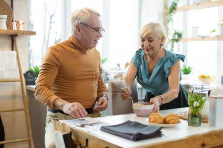 Photo pour Je prends un petit déjeuner. Charmante épouse aimante aux cheveux gris portant un haut élégant donnant un petit déjeuner à son beau beau beau conjoint vieillissant - image libre de droit