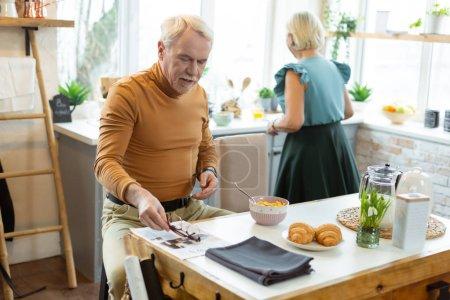 Photo pour Conjoints âgés à la cuisine. attrayant joyeux beau beau homme barbu aux cheveux blancs en pull jaune assis à la table tandis que son élégant conjoint vieillissant attrayant cuisine à la cuisine . - image libre de droit
