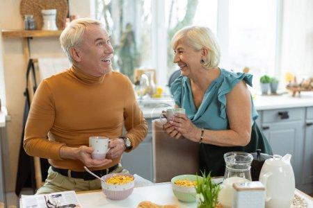 Photo pour Bon couple petit déjeuner. Joyeux sourire lumineux contesté vieux couple marié aux cheveux gris portant des vêtements élégants partageant un rire tout en prenant le petit déjeuner à la cuisine - image libre de droit