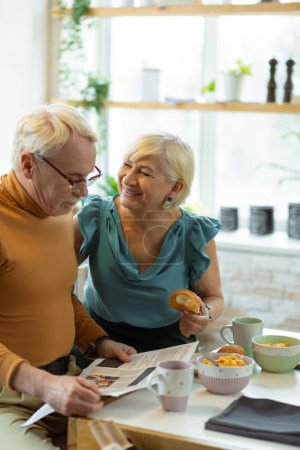 Photo pour Petit déjeuner à la cuisine. Rayonnant bienveillants joyeux joyeux soutenu souriant bien habillé vieillissement conjoints heureux aux cheveux blancs profiter d'un savoureux petit déjeuner et la conversation tout en étant assis à la cuisine - image libre de droit