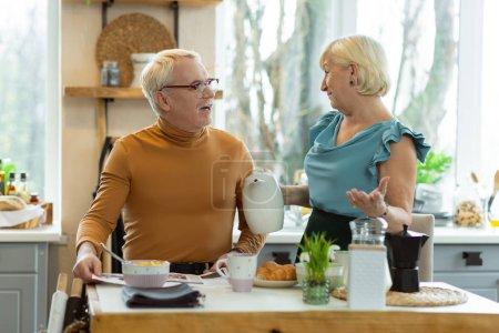 Photo pour Parler pendant le petit déjeuner. Joyeux attrayant joyeux attrayant attrayant attrayant couple aux cheveux blancs émotionnel dans les années avancées parler pendant le petit déjeuner tout en étant assis à la cuisine . - image libre de droit
