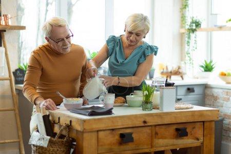 Photo pour Verser le thé dans des tasses. Genre soins rayonnant vieux cheveux gris séduisante élégante femelle en haut azur verser du thé dans les tasses pour son beau poil blanc vieillissement barbu beau conjoint . - image libre de droit