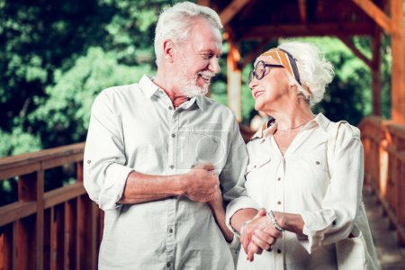Photo for Walking outdoors. Face portrait of elderly appealing alluring cheerful happy joyful aging couple lovingly looking at each other during a walk outdoors - Royalty Free Image
