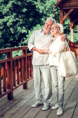 Photo pour Cuddling épouses vieillissantes. attrayant joyeux joyeux attentionné cheveux argentés vieillissement mâle câlinant tendrement l'élégant à la mode vieux beau conjoint tout en marchant sur le pont en bois . - image libre de droit