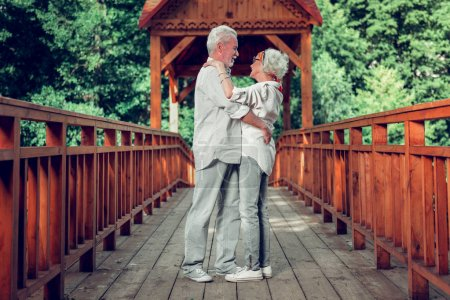 Photo for Embracing aging couple. Full-sized of beautiful loving caring appealing elderly white-haired spouses standing on the bridge and embracing each other - Royalty Free Image