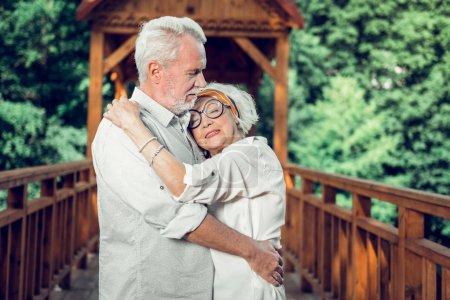 Photo pour Un couple de câlins depuis des années. Gros plan portrait de femme âgée aux cheveux blancs à la mode dans des lunettes serrant tendrement le beau vieillard attrayant barbu conjoint joyeux à l'extérieur - image libre de droit