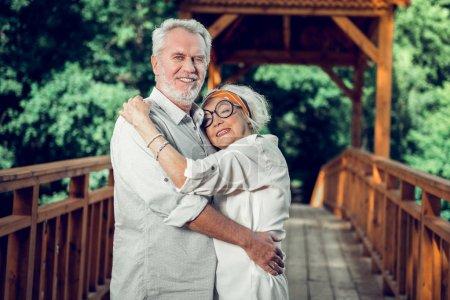 Photo pour Câlins tendres. Portrait du visage de la femme aux cheveux argentés à la mode dans des lunettes de vue à la mode embrassant amoureusement le beau beau conjoint rayonnant souriant barbu depuis des années à l'extérieur - image libre de droit