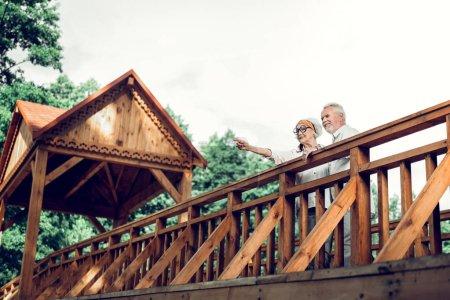 Photo pour Femme et mari. Joyeux attrayant beau beau joyeux vigoureux délicieux vieillissement élégant conjoint et des lunettes de vue élégantes debout sur le pont avec beau aux cheveux blancs bel homme ensemble - image libre de droit