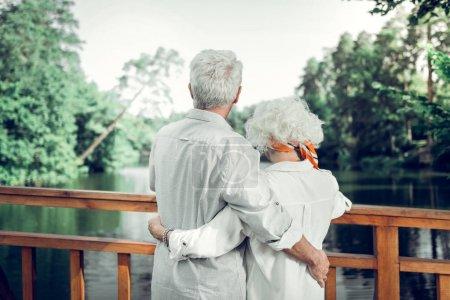 Photo pour Quelques photos de dos. Photo arrière de beau couple aimant les cheveux blancs aimant porter des vêtements blancs serrant tendrement les uns les autres . - image libre de droit