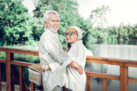 Photo pour Un couple avec panier pique-nique. Délicieux souriant séduisant à la mode joyeuse vieille femme portant des lunettes câlinant un beau mari aux cheveux argentés gardant un panier en osier pique-nique dans les mains - image libre de droit
