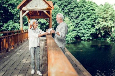 Photo pour Conjoints avec un signe cardiaque. Rayonnant lumineux souriant soutenu joyeux élégant mari aîné et femme portant correspondant regards tenant un signe de coeur dans les mains tout en se tenant sur le pont en bois - image libre de droit