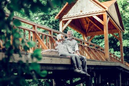 Photo pour Homme et femme sur le pont. Aimer soigner heureux souriant joyeux rayonnant blanc cheveux vieux homme et femme regardant tendrement l'autre tout en étant assis sur le pont . - image libre de droit