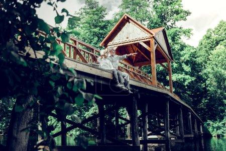Photo pour Assis au pont. Rayonnant lumineux délicieux amusé joyeux agréable attrayant mari et femme aux cheveux gris assis sur le pont en bois et profiter de la nature - image libre de droit