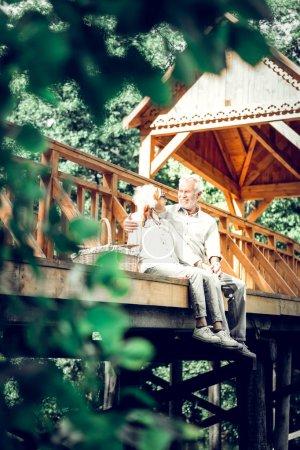 Photo pour Être sur le pont. Aimer soigner joyeux élégant souriant rayonnant argent cheveux vieux homme et femme portant des vêtements modish avoir la conversation tout en étant assis au pont en bois - image libre de droit