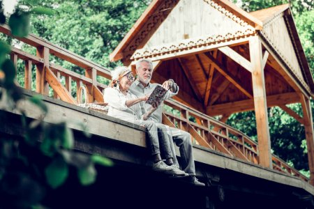 Photo for Enjoying the book. Merry happy stylish glowing loving beaming white-haired married couple in years wearing white clothes enjoying a book on the wooden bridge - Royalty Free Image