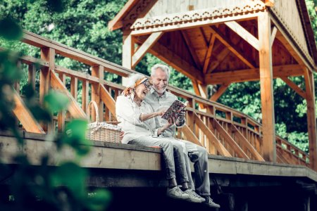 Photo for Reading a book. Carefree stylish glowing beautiful beaming silver-haired married couple in advanced years wearing stylish clothing reading a book on the wooden bridge - Royalty Free Image