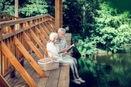 Photo for Time outdoors. Grinning glowing satisfied vigorous delightful white-haired spouses well in years sitting on the bridge outdoors and reading a book together - Royalty Free Image