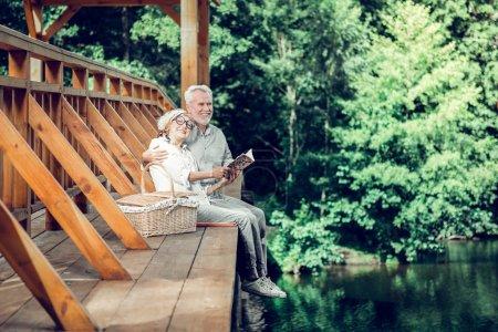 Photo pour Temps sur le pont. Faisant appel souriant heureux soutenu à la mode belle charmante conjoints âgés avec gris coiffure courte passer un bon moment tout en lisant un livre ensemble - image libre de droit