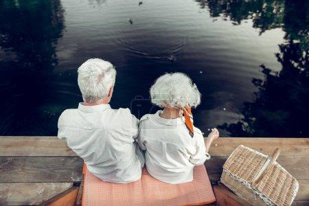 Photo pour Photo arrière d'un couple. Plan arrière de belles épouses séduisantes âgées aimantes dans les années avec une coiffure courte blanche passer du temps sur le lac - image libre de droit