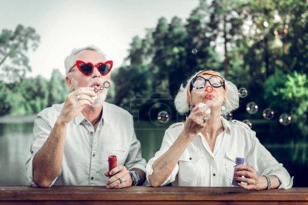 Photo pour Des bulles. Joyeux joyeux rayonnant lumineux charmant beau couple âgé aimant dans des lunettes de soleil drôles soufflant des bulles à l'extérieur - image libre de droit