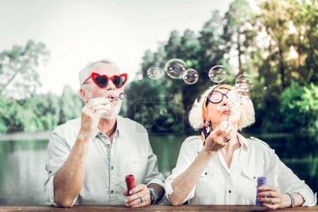 Photo pour Couple âgé soufflant des bulles. Portrait du visage de joyeux rayonnage joyeux soutenu agréable attrayant homme âgé et femme portant des lunettes de soleil drôles se livrant à souffler des bulles à l'extérieur - image libre de droit