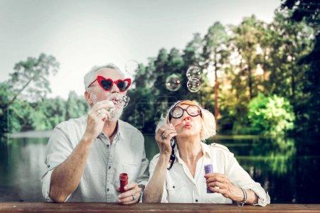 Photo pour Des bulles qui soufflent. Gros plan portrait de joyeux contesté heureux charmant beau faisceau affectueux attentionné mari âgé et femme portant des lunettes de soleil élégantes s'amuser tout en soufflant des bulles - image libre de droit
