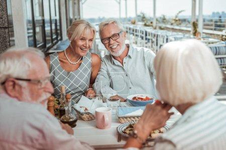 Photo pour De bonne humeur. Joyeux blonde femme démontrant son sourire tout en passant du temps avec des amis - image libre de droit