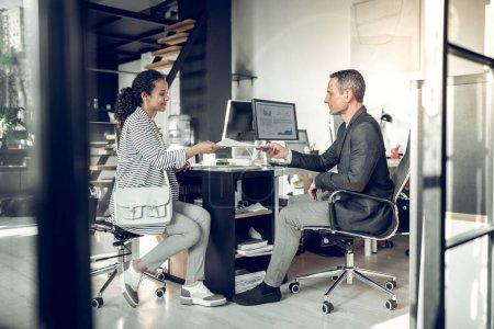 Photo pour Un homme d'affaires qui prend un CV. Homme d'affaires prenant CV de jeune belle femme avant l'entrevue d'emploi - image libre de droit