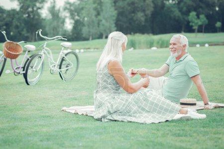 Photo pour Merci, ma chère. Femme joyeuse positive regardant son mari tout en lui prenant son cadeau - image libre de droit