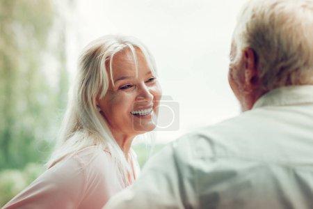 Photo pour Conversation agréable. Joyeuse femme heureuse parlant avec son mari tout en profitant de son temps avec lui - image libre de droit